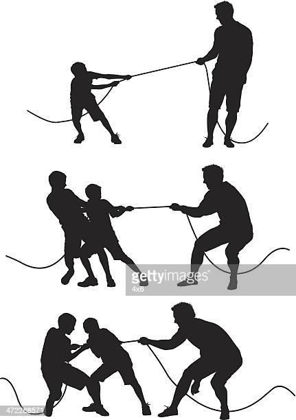 Homme jeu de tir à la corde avec des enfants