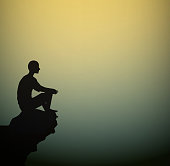 man sits on the rock look at the empty space of the break, meditation man silhouette