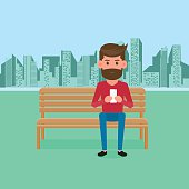 Man sitting on bench in the park with smartphone.Online communication