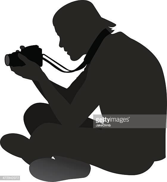 Man Sitting on Ground with Camera