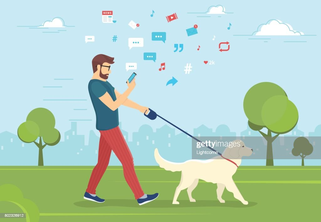 Man walking with dog outdoors in park and using smartphone to read news