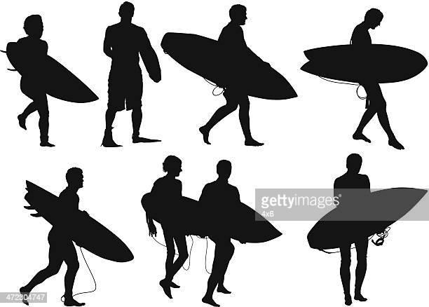 man walking with surfboard - surfboard stock illustrations