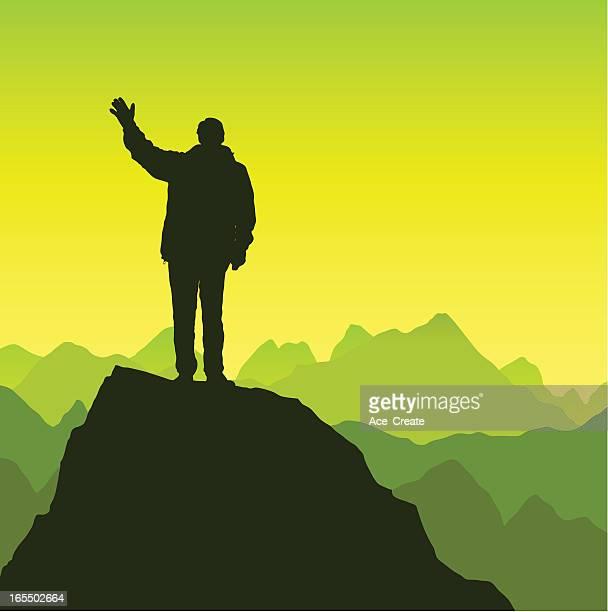 Man waving on a mountain top