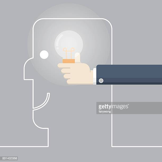 Man's hand putting lightbulb into the head of a businessman