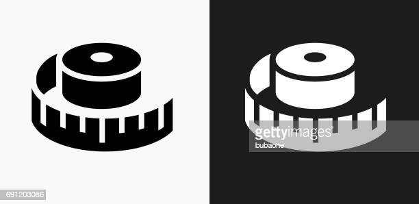 measuring tape icon on black and white vector backgrounds - tape measure stock illustrations