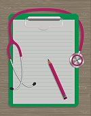 medical stethoscope, note pad and pencil on wood texture