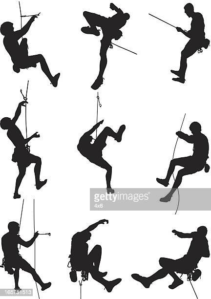 men rappelling and rock climbing - rock climbing stock illustrations, clip art, cartoons, & icons