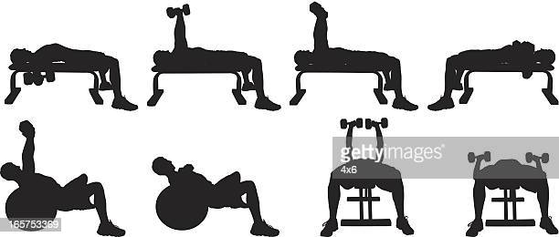 Men working out with dumbbells on a weight bench