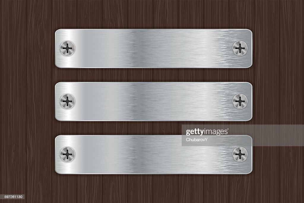 Metal plates on wooden background