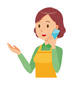 A middle-aged housewife wearing an apron is calling by smart phone