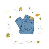 Modern fashion blue jeans. Clothing on the background of autumn leaves and drops of watercolor. Hand drawn vector illustration on a white background.