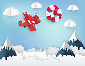Modern paper art origami background. Red airplane with bunch of paper heart balloons, fluffy clouds, high mountains and place for text.