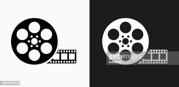 movie reel icon on black and white vector backgrounds - film stock illustrations, clip art, cartoons, & icons