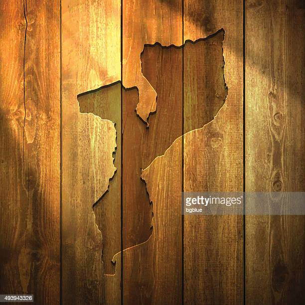 mozambique map on lit wooden background - mozambique stock illustrations, clip art, cartoons, & icons