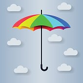 Multi-colored umbrella on a gray background with clouds
