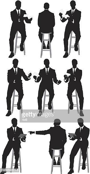 Multiple silhouette of businessman sitting on stool