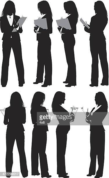 Multiple silhouettes of businesswoman with clipboard