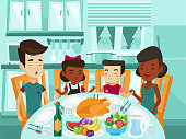 Multiracial family praying at festive table