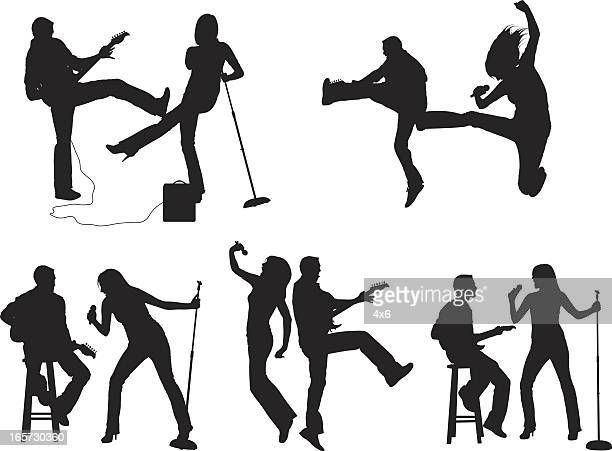musical couple playing and singing on stage - microphone stand stock illustrations