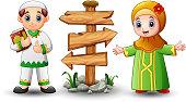 Muslim boy cartoon holding quran with girl and blank wood arrow sign