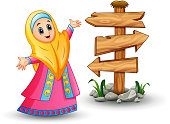 Muslim girl wearing yellow veil and pink dress presenting with blank wood arrow sign