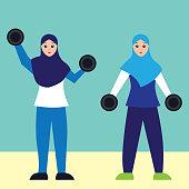 Muslim woman wearing a hijab at the gym lifting handweights