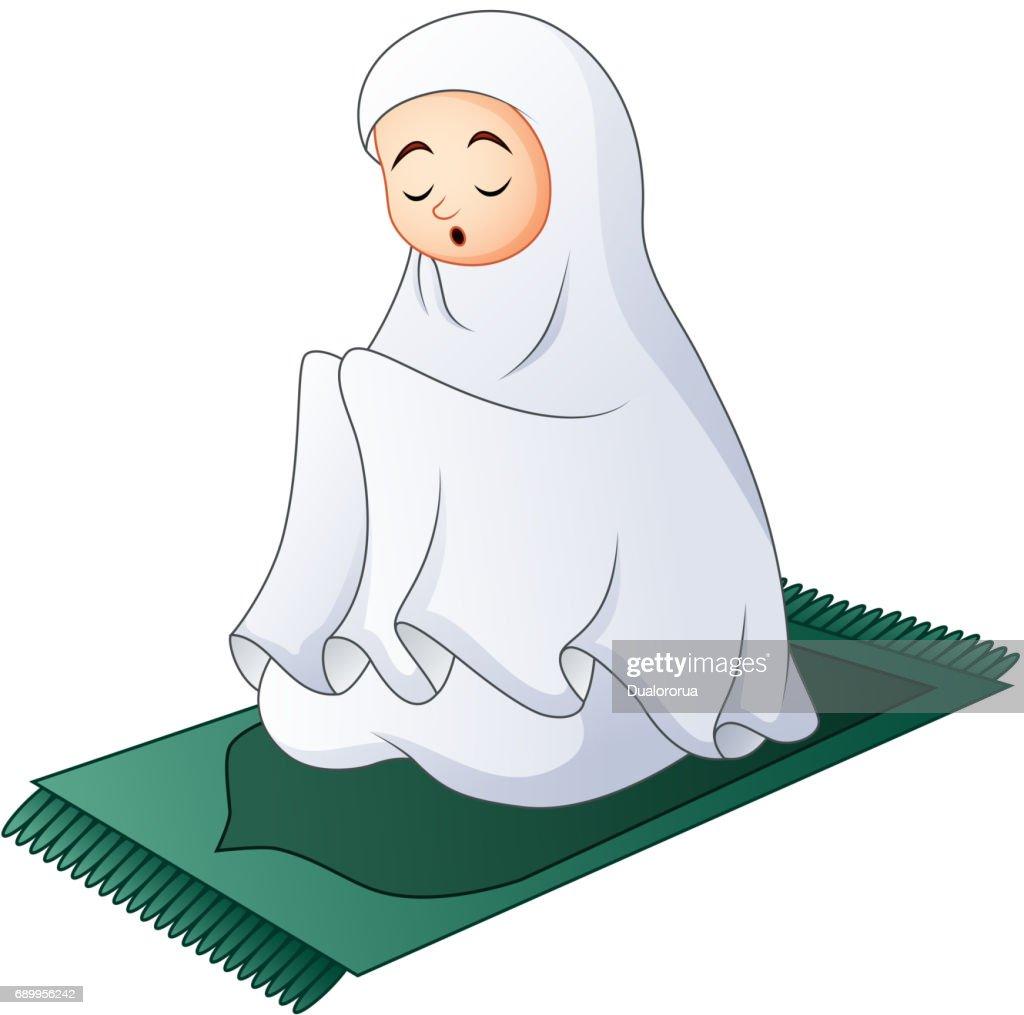 Muslim women sitting on the prayer rug while praying