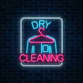 Neon dry cleaners glowing sign with hanger and shirt on a dark brick wall background. Cleaning service signboard
