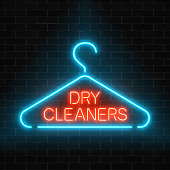 Neon dry cleaners glowing sign with hanger on a dark brick wall background.