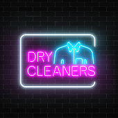Neon dry cleaners glowing sign with shirt in rectangle frame on a dark brick wall background.
