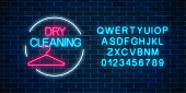Neon dry cleaning glowing sign with hanger in circle frame with alphabet. Cleaning service signboard design.