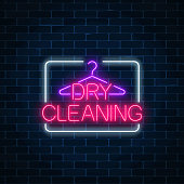 Neon dry cleaning glowing sign with hanger on a dark brick wall background. Cleaning service signboard design.