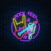 Neon rock festival sign with guitar, microphone and rock gesture in round frame. Live music in open air icon.