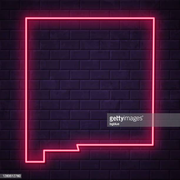 new mexico map - glowing neon sign on brick wall background - new mexico stock illustrations