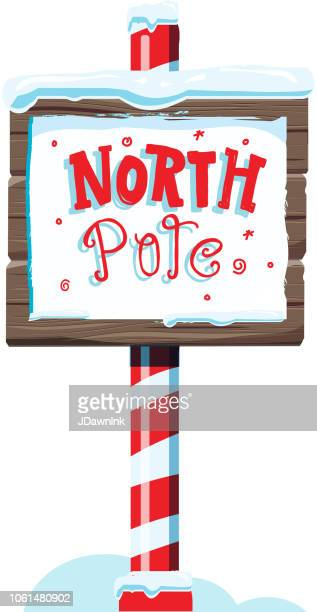 north pole wooden winter sign with handwriting or hand lettered text - north pole stock illustrations, clip art, cartoons, & icons