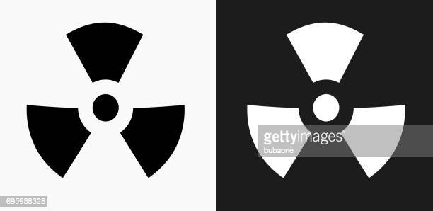 nuclear sign icon on black and white vector backgrounds - radioactive contamination stock illustrations
