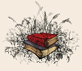 Occult books, surrounded by wildflowers and plants.