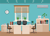 Office room interior including two work spaces with cityscape outside window.