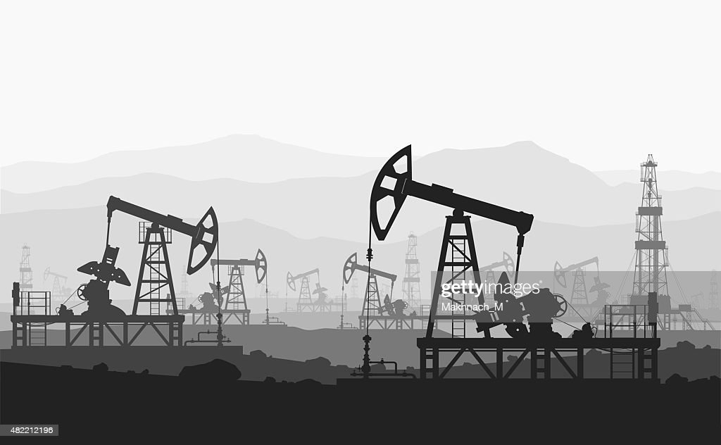 Oil pumps at large oilfield over mountain range.