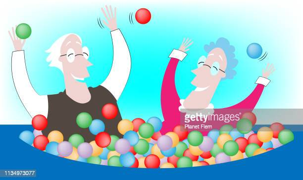 Oud echtpaar spelen in een bal zwembad