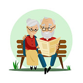Old couple sitting on a bench in the park