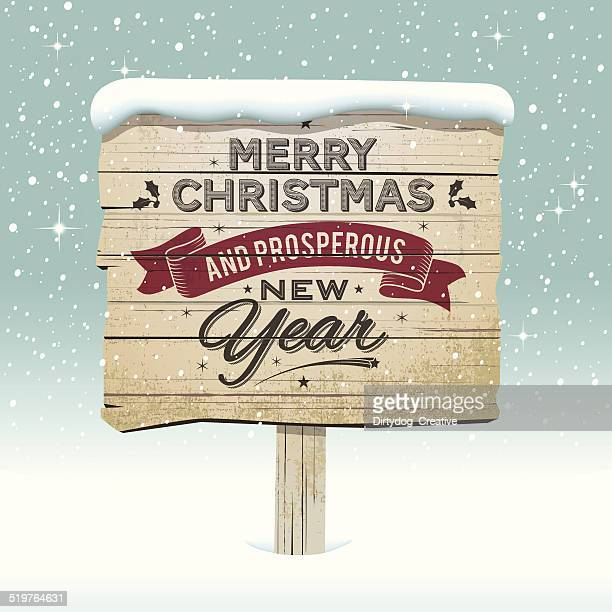 Old vintage wooden Christmas sign in the snow