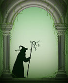 old wizard in the arch of the castle garden, Halloween character, forest sorcerer, fairytale character,