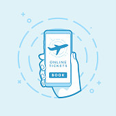 Online Book button and airplane icon on screen. Hand holding smartphone.