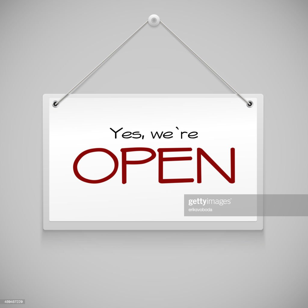 Open sign with red letters hanging on gray wall