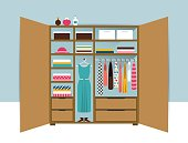 Open wardrobe. Wooden closet with tidy clothes, shirts, sweaters, boxes
