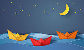 origami boat sailing in blue ocean at night , paper art style