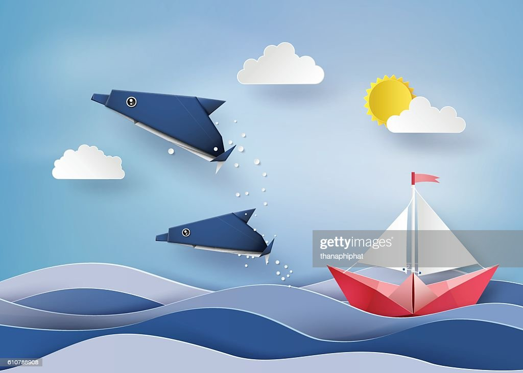 Origami made dolphin and sailing boat Float on sea  .