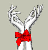 Pair of female hands bound by a red ribbon with a bow
