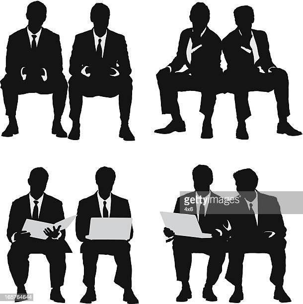 pair of young businessmen sitting - close to stock illustrations